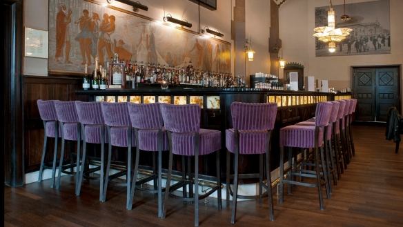Le comptoir de bar du Café Américain d'Amsterdam est adossé à une grande fresque. Crédit photo Café Américain.