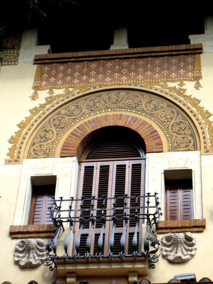 Juxtaposition de motifs décoratifs : peinture au-dessus de l'arc de la porte-fenêtre, ferronnerie de l'escalier, coquilles sous les fenêtres latérales.