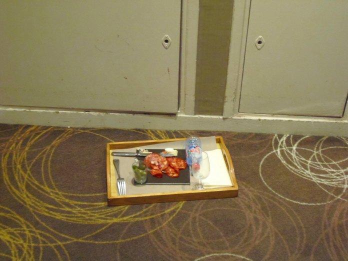 Devant les armoires techniques d'un couloir, à proximité des ascenseurs.