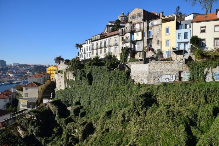 depuis le pont Luis I la végétation drape les ruines au-dessus du quai de la Ribeira à porto portugal